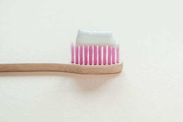 歯磨き粉が付いたピンクの竹の歯ブラシのクローズアップ、ゼロウェイストコンセプトの歯科治療、持続可能なライフスタイル