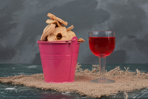 Pink basket with dried fruits and glass of juice on marble wall .