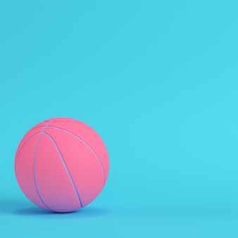 Pink basketball ball on bright blue background
