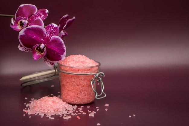 Vinous 배경에 난초 꽃과 핑크 목욕 소금. 고품질 사진