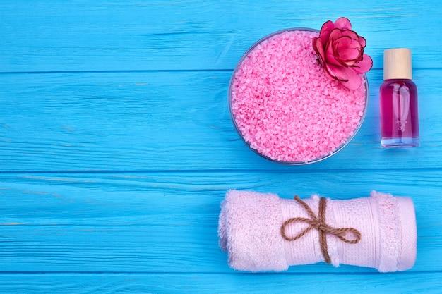 압연 수건과 로션 병이 있는 분홍색 목욕 소금. 평면도 평면도. 푸른 나무 배경입니다.
