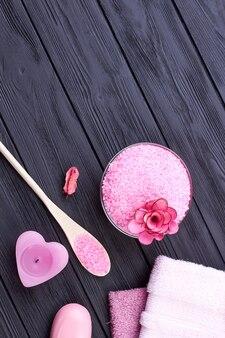 어두운 나무 테이블에 분홍색 욕실 스파 액세서리입니다. 수직 샷 평면도 평면도.