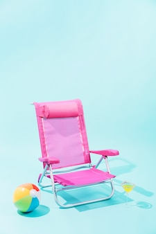 Pink beach chair, colorful beach ball and yellow drink in elegant glass on light blue background
