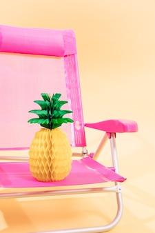 Розовый шезлонг с бумажным ананасом на светло-оранжевом фоне