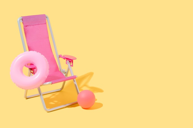 A pink beach chair with a float and a ball on yellow background summer and travel 3d illustration