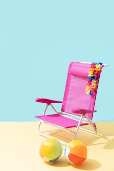 Pink beach chair with two beach balls and a flower necklace on fake sand and light blue background