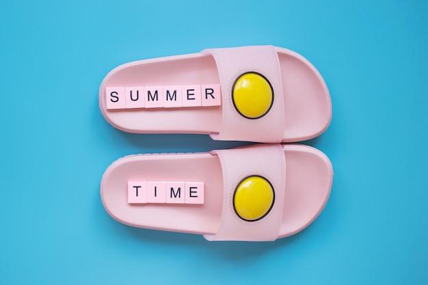 青い背景の上のピンクのビーチスリッパ夏のビーチでの休暇と旅行の概念
