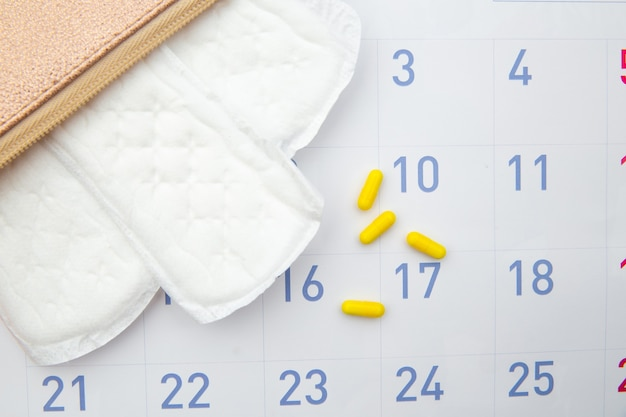 Pink beautician with daily cotton sanitary pads and hormonal contraceptive on calendar.