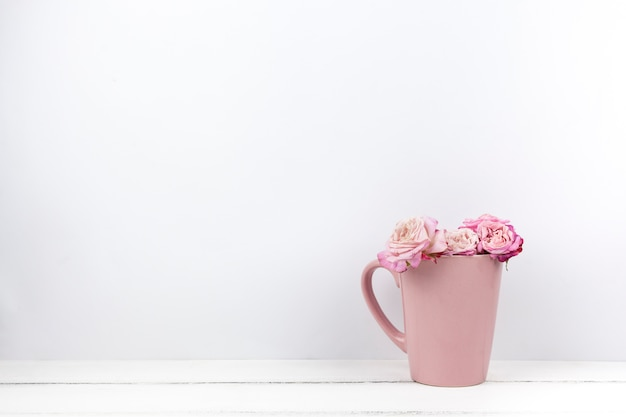 Pink beautiful roses in ceramic mug at home