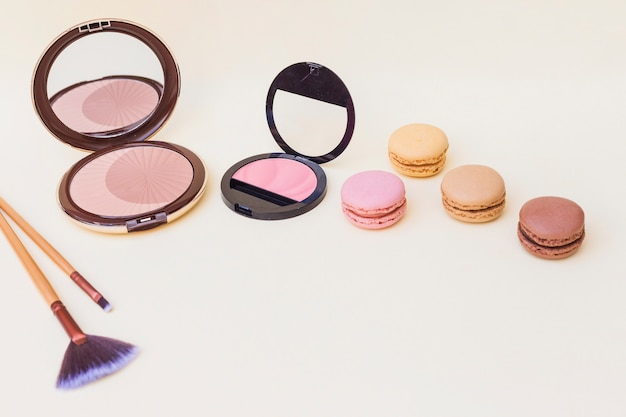 Pink and beige blusher and makeup brush with macaroons on colored background