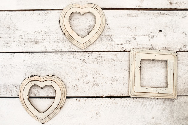 Pink, beige old photo frames on a wooden background. in the shape of a heart. wall, interior.
