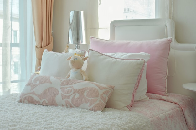 Pink and beige pillows on bed next to window