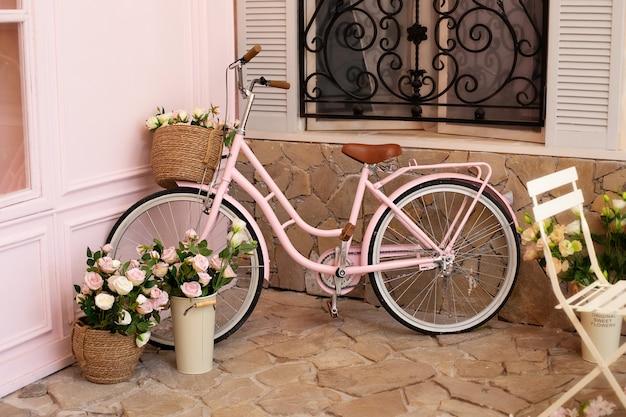 花束の花が付いているバスケットが付いているピンクの自転車は通りの喫茶店に立っています。エコ輸送。
