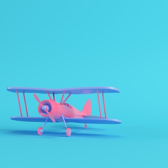 Pink biplane on bright blue background in pastel colors. minimalism concept