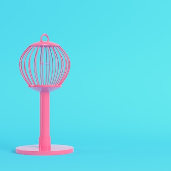 Pink bird cage on bright blue in pastel colors