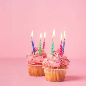 Pink birthday cupcake wit lit candles