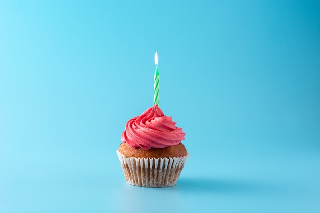 Pink birthday cupcake with green candle on blue background
