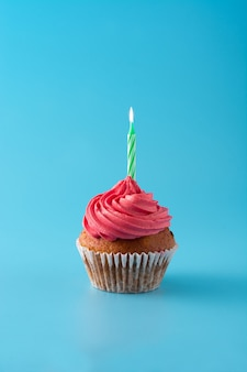 Pink birthday cupcake with green candle on blue wall