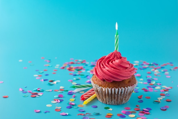 Pink birthday cupcake with green candle and confetti on blue background