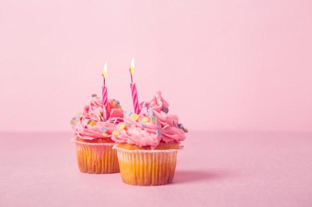 ピンクの誕生日カップケーキと点灯キャンドル