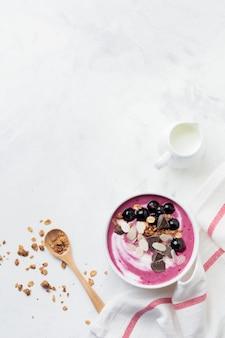 Розовые ягоды черной смородины, банановый смузи с мюсли, хлопья из миндаля и шоколада на светло-сером бетонном фоне