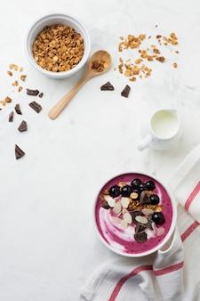 Розовые ягоды черной смородины, банановый смузи с мюсли, миндальные хлопья и шоколад на светло-серой бетонной поверхности