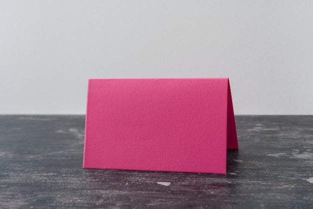 Pink blank card on dark table.