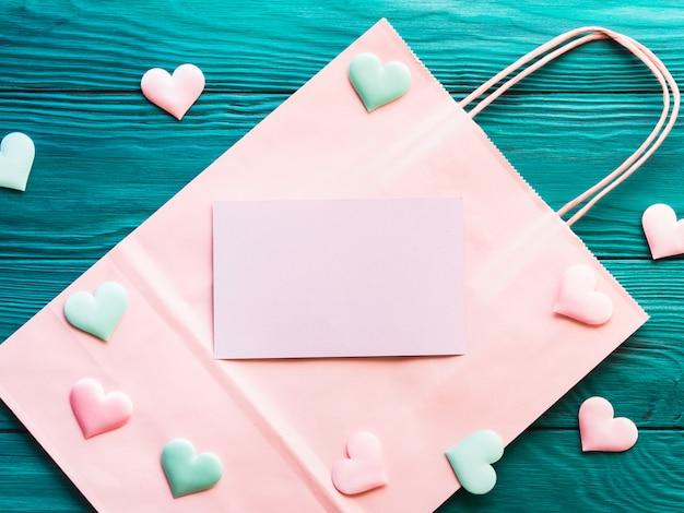 Розовая пустая карточка на корзине с сердечками