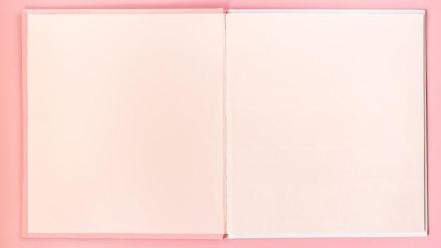 ピンクの空白のページはピンクのテーブルに本をスケッチします