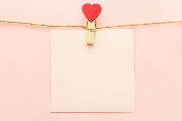 Pink blank paper sheet on a clothes line and clothespegs with red heart on a pink