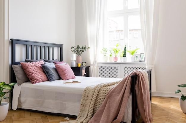 식물과 창문이 있는 밝은 침실 내부에 검은색 헤드보드가 있는 침대에 분홍색 담요. 실제 사진