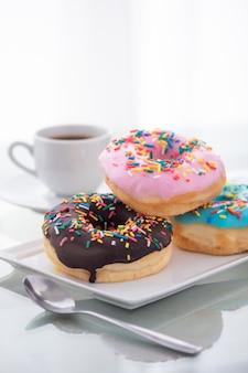 Розовые, голубые и шоколадные пончики на белой тарелке и чашка кофе на свету