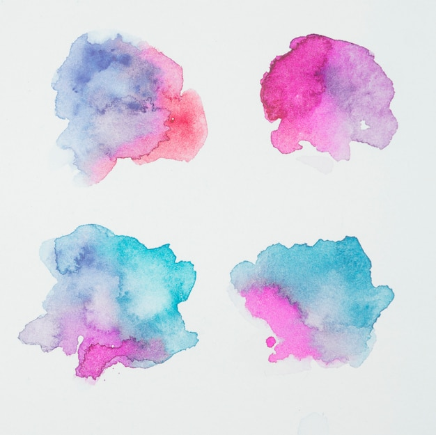 Pink, blue and aquamarine blots of paints on white paper