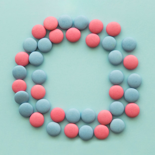 Pink and blue candies arranged in circular shape over the colored backdrop