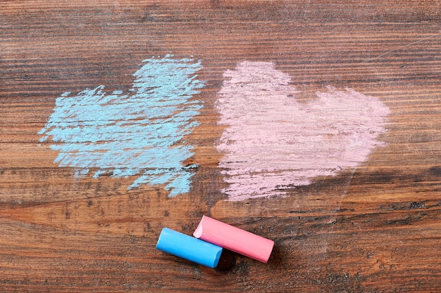 Pink and blue chalk hearts. chalk sticks on wooden backdrop. cute art surprise.