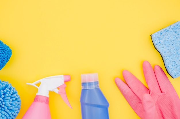 Pink and blue cleaning supplies on yellow backdrop
