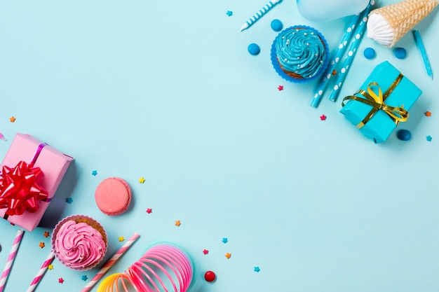 Pink and blue colored party items with confectionery on colored backdrop
