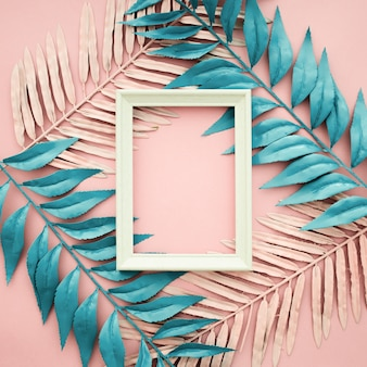 Pink and blue leaves on pink background with blank frame