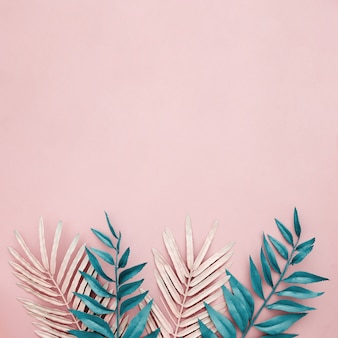 Pink and blue leaves on pink background with copyspace on top side