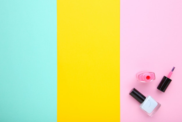 Pink and blue nail polishes on colorful background