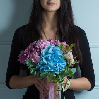 Pink and blue tonned flower bouquet in the hands of a woman