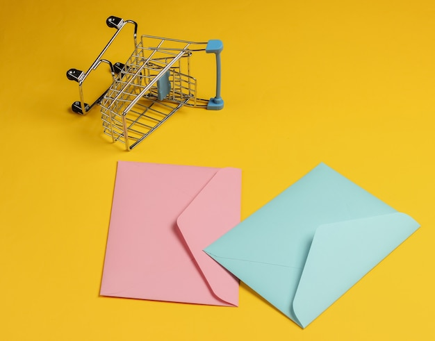 Pink and blue two envelopes and shopping trolley on yellow background. mockup for valentines day, wedding or birthday