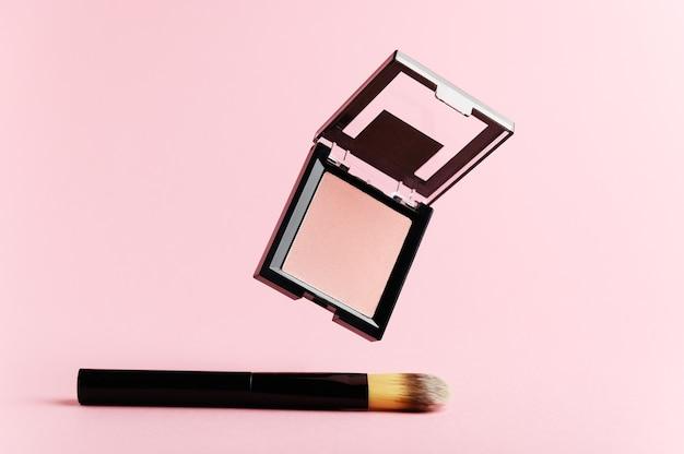 ピンクのチークと黒の化粧ブラシ
