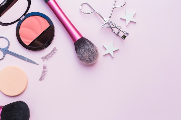 Pink blusher; sponge; scissors; eyelashes; eyelash curler and makeup brush on pink background