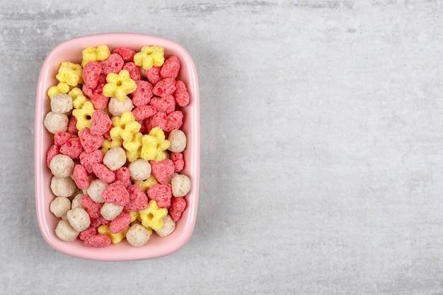 Un bordo rosa pieno di cereali colorati per la colazione posto su un tavolo di pietra.