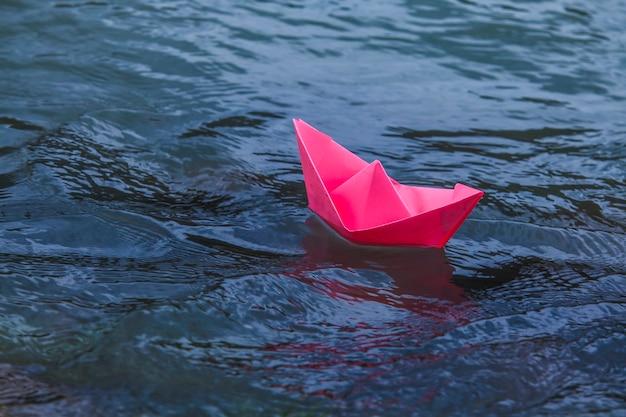 流れに乗って青い海に浮かぶピンクのボート