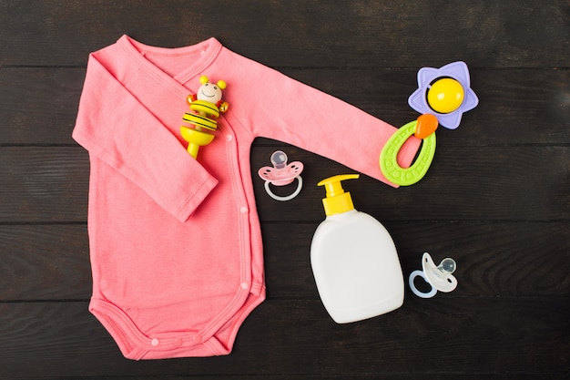 Розовый боди с двумя погремушками и двумя сосками-пустышками с детским мылом на коричневом деревянном столе