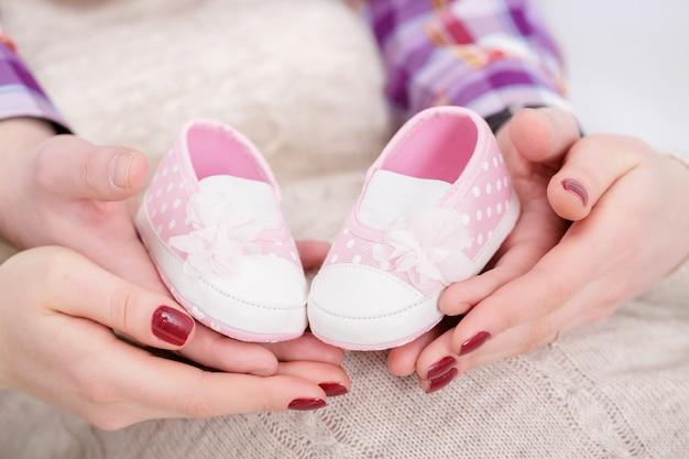 Розовые пинетки для новорожденного в руках мамы и папы. беременность