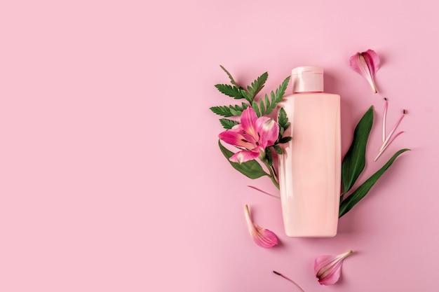 Розовая бутылка с увлажняющим кремом на розовом фоне с цветами альстромерии. макет косметического контейнера с местом для текста. концепция продукта красоты натуральный уход за кожей.
