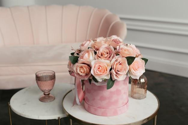 白いコーヒーテーブルの上のベルベットのピンクのボックスのピンクの花束